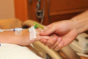 Person holding patient's hands with IV's and bandages, comforting Medical Negligence victim