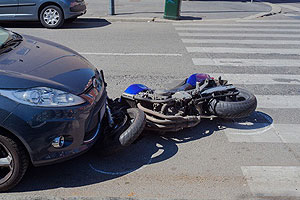 Motorcycle underneath car after crash